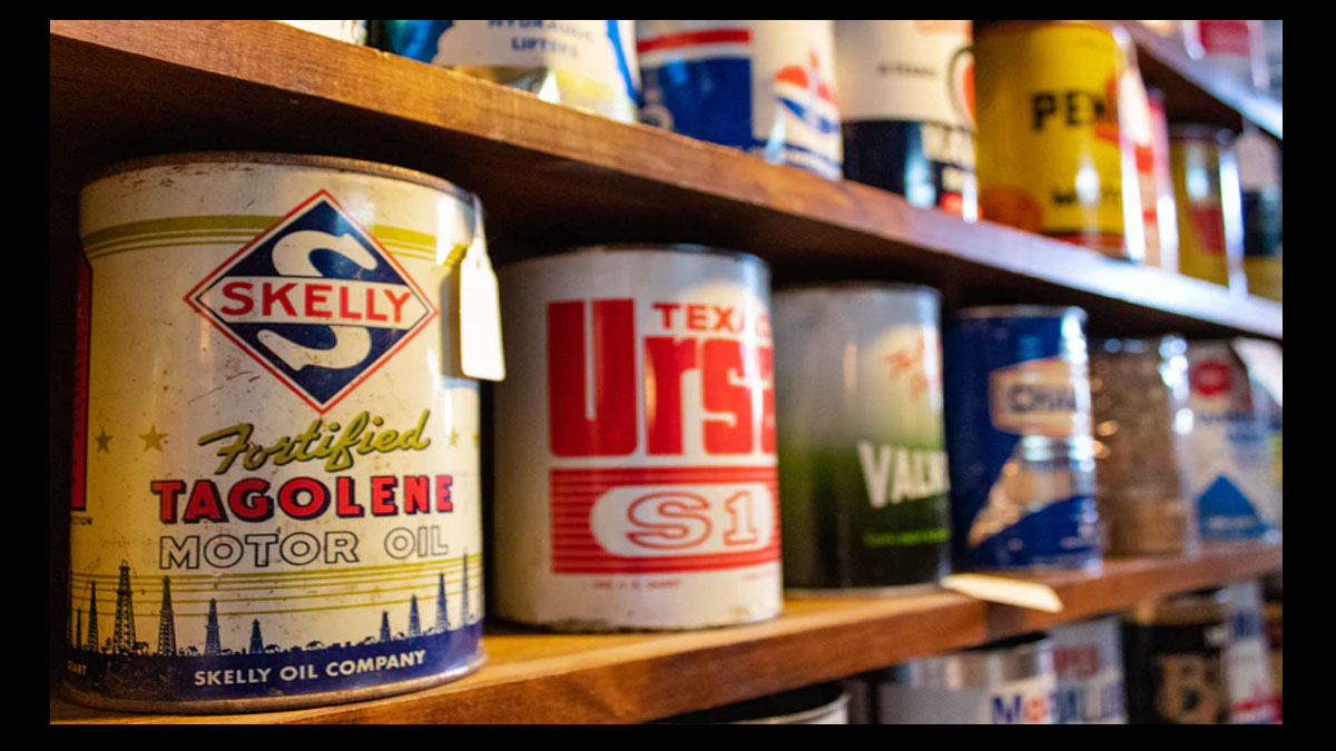old oil and paint cans on shelf